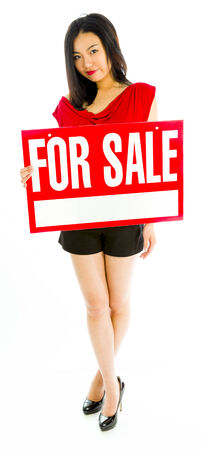 Saleswoman holding a for sale sign