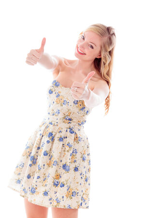 Beautiful young woman standing and showing thumbs up sign with both hands photo