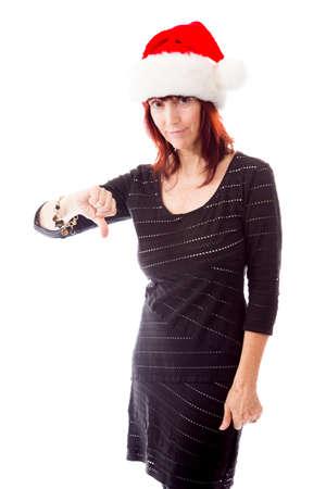 wearing santa hat: Mature woman wearing Santa hat and showing thumbs down sign
