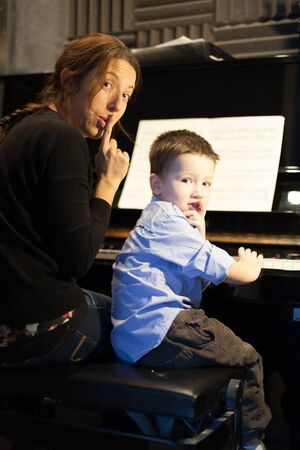 Boy putting index finger on lips with his piano instructor Imagens