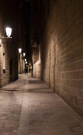 Empty narrow alley illuminated by street lamps at night, Barcelona, Catalonia, Spain Stock Photo