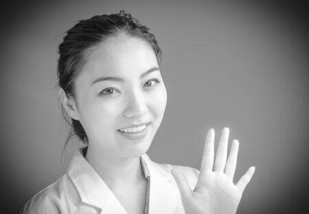 labcoat: Attractive asian girl in her twenties isolated on a plain background, black and white image shot in a studio Stock Photo