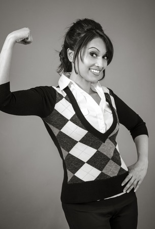 only the biceps: Adult indian woman in studio isolated on grey background, black and white image Stock Photo