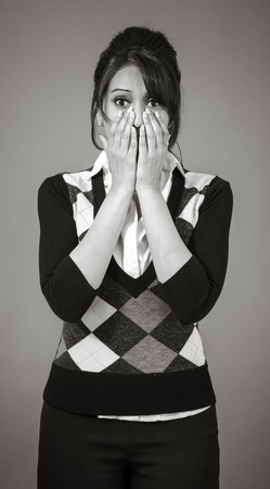 raised eyebrow: Adult indian woman in studio isolated on grey background, black and white image Stock Photo