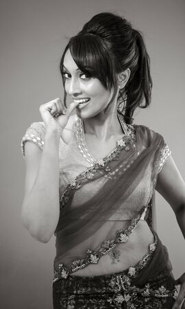 desires 25: Adult indian woman in studio isolated on grey background, black and white image Stock Photo