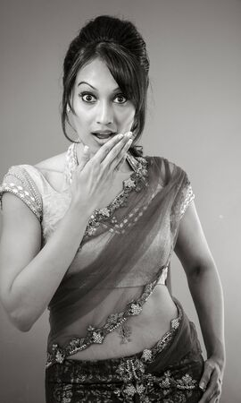 disbelieve: Adult indian woman in studio isolated on grey background, black and white image Stock Photo