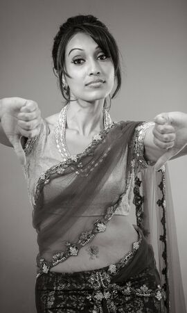 downcast: Adult indian woman in studio isolated on grey background, black and white image Stock Photo