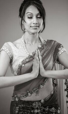 namaskar: Adult indian woman in studio isolated on grey background, black and white image Stock Photo