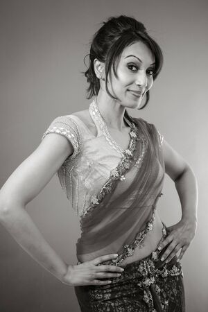 arms akimbo: Adult indian woman in studio isolated on grey background, black and white image Stock Photo