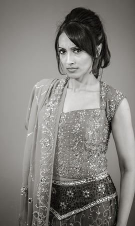 allegation: Adult indian woman in studio isolated on grey background, black and white image Stock Photo
