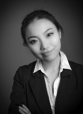 the twenties: Attractive asian girl in her twenties isolated on a plain background, black and white image shot in a studio Stock Photo