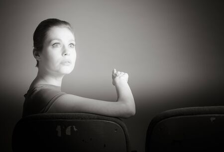 Attractive caucasian woman in the theatre in her 30 isolated on a grey background, black and white image photo