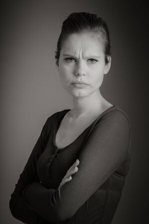 grey background: Attractive caucasian woman in her 30 isolated on a grey background, black and white image Stock Photo