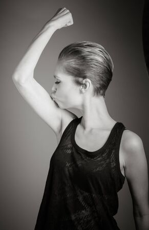 only the biceps: Attractive caucasian woman in her 30 isolated on a grey background, black and white image Stock Photo