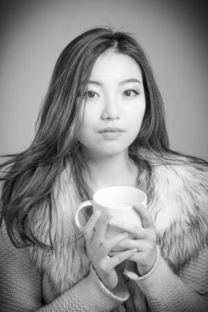 Attractive asian girl in her twenties isolated on a plain background, black and white image shot in a studio photo