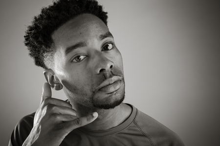 call out: Attractive afro-american man posing in a  studio isolated on a background, black and white image Stock Photo