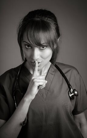 Attractive Indian doctor woman posing in a studio in front of a background, black and white image photo
