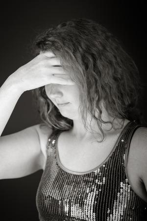ashamed: modelo aislado en fondo liso avergonzado el rostro escondido en la mano