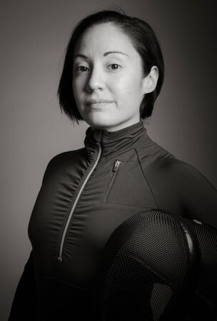 25 29 years: Portrait of a female fencer wearing fencing uniform and holding