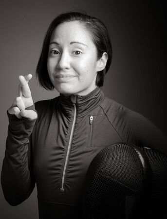 crossing fingers: Female fencer wishing with crossing fingers