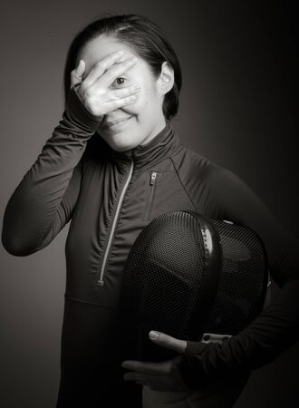 covering the face: Female fencer peeking through hands covering face