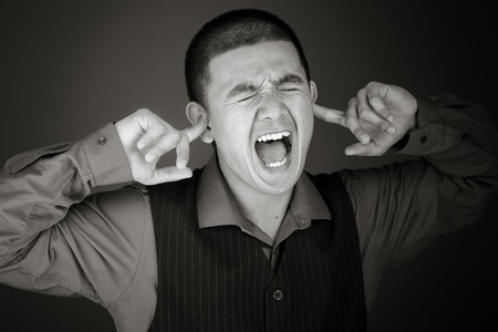 Model isolated on plain plugging ears with fingers