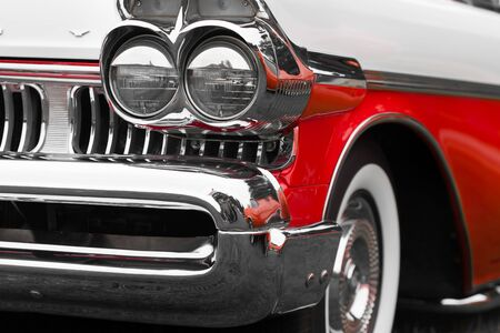 shiny car: Close-up of right headlights of a red and white shiny classic vintage car Stock Photo