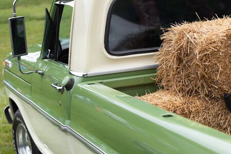 camioneta pick up: Hay bales loading on green pick-up truck in farm