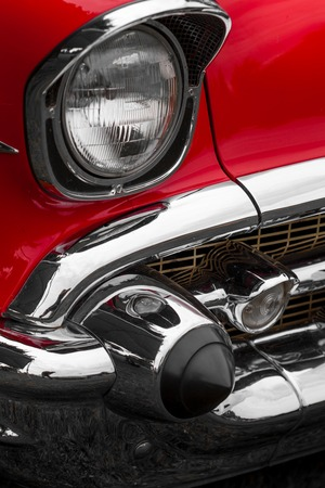 shiny car: Close-up of left headlight of a red shiny classic vintage car