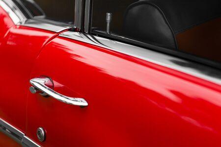 car door: Close-up of car door lock pin of a red shiny classic vintage car