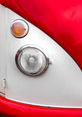 shiny car: Close-up of headlight of a white and red shiny classic vintage car