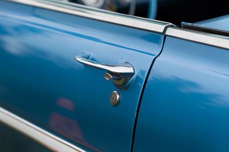 car door: Close-up of car door of a blue shiny classic vintage car