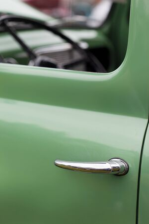 shiny car: Close-up of car handle of a green shiny classic vintage car