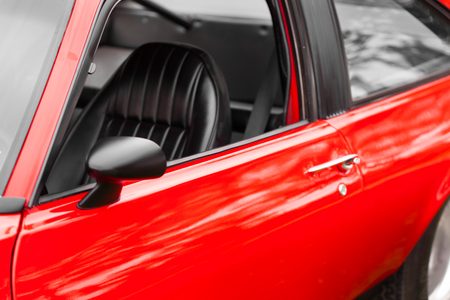 shiny car: Black seat of a red shiny classic vintage car