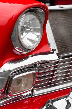 shiny car: Close-up of left headlights of a red shiny classic vintage car Stock Photo