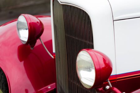 shiny car: Close-up of headlights of a red and white shiny classic vintage car