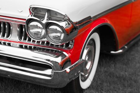 shiny car: Right headlights of a red and white shiny classic vintage car