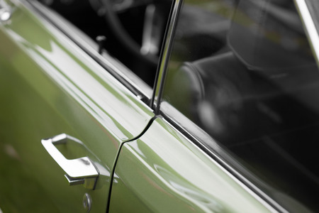 shiny car: Car handle of a green shiny classic vintage car