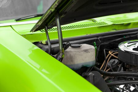 shiny car: Open bonnet of a green shiny classic vintage car Stock Photo