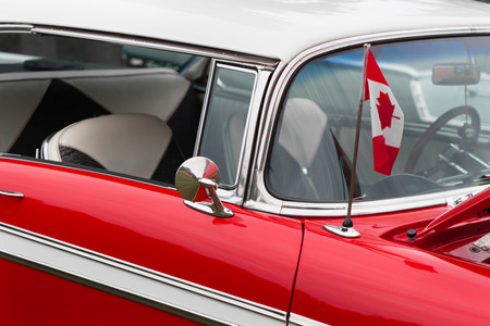 Canadian flag on bonnet of a red classic vintage car