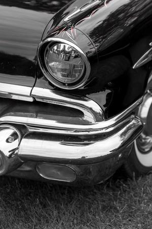 shiny car: Close-up of right headlight of a black shiny classic vintage car Stock Photo