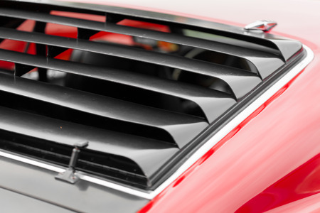 Close-up of wind radiator grille of a red shiny classic vintage car