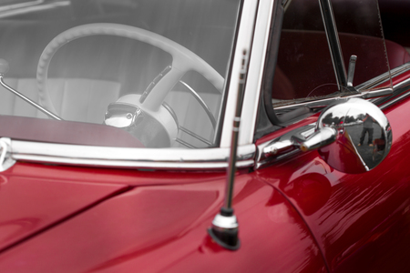 shiny car: Steering wheel of a maroon shiny classic vintage car
