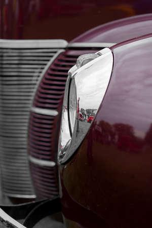 shiny car: Close-up of headlight of a maroon shiny classic vintage car Stock Photo