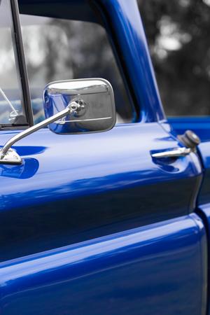 Close-up van buitenspiegel van een blauwe glanzende klassieke uitstekende auto