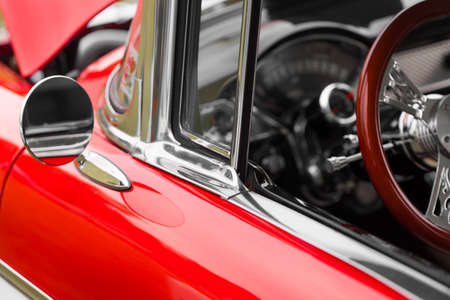 Wing mirror of a red shiny classic vintage car Imagens