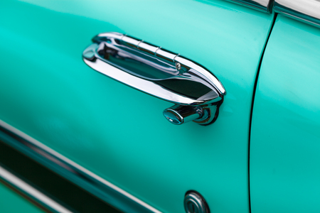 shiny car: Close-up of car handle of a turquoise shiny classic vintage car