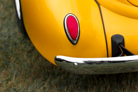 tail light: Close-up of tail light of a yellow shiny classic vintage car