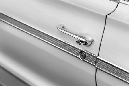car door: Close-up of car door handle of a white shiny classic vintage car