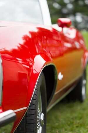 differential focus: Close-up of tyre of a red shiny classic vintage car